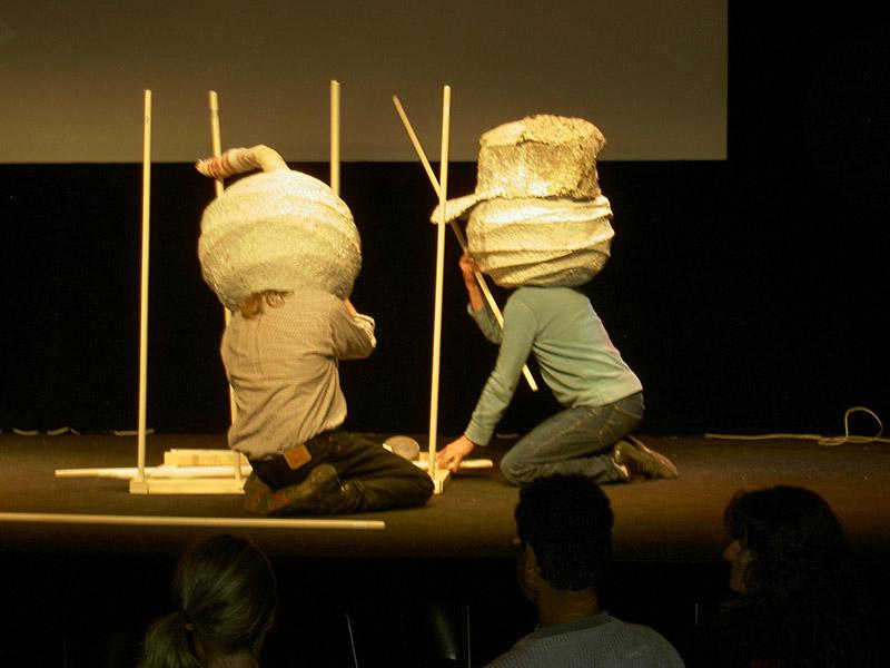 två konstnärer performance med lampor som huvuden
